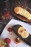 Een chocoladedessert met gesneden bananen en aardbeien en sappig stock afbeelding