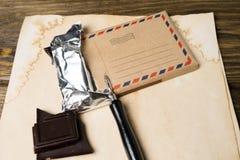 Een chocoladereep en een vulpen liggen op uitstekend document, een oude houten lijst Spot omhoog royalty-vrije stock foto's