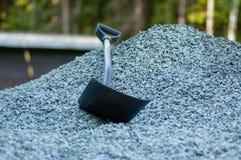 Een chovel in een stapel van grijs grint Stock Fotografie