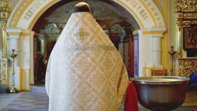 Een Christelijke bejaarde priester in feestelijke kledij met glazen bidt stock video