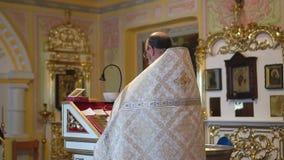 Een Christelijke priester in feestelijke kledij met glazen bidt stock video