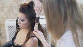 Een close-up, bebouwd kader, een mooi jong brunette met een diepe halslijn zit als voorzitter van een kapper, doet haar stock videobeelden