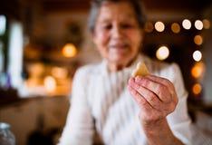 Een close-up die van bejaarde cakes in een keuken maken thuis, een koekje houden stock fotografie