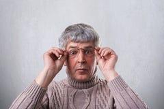 Een close-up die van de verbaasde hogere mens glazen dragen en sweater die zijn handen op de kaders van glazen houden die met bre Stock Afbeeldingen