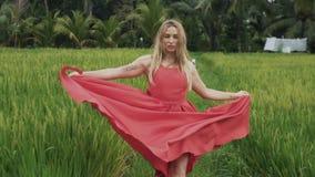 Een close-up die van een jong meisje die langs een padieveld lopen, haar zijde stromende rok golven, de wind ontwikkelt haar haar stock footage