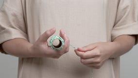Een close-up die van vrouwen` s handen een broodje van gestreepte kabel houden Zij trekt de kabel en wikkelt het af stock footage