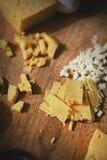 Een close-up sneed kaas en het knoflook is op de scherpe raad op de lijst Royalty-vrije Stock Fotografie