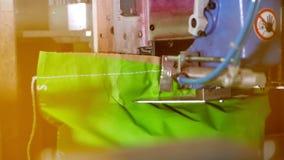 Een close-up, een speciale automatische machine naait omhoog, naait, kartonzakken met producten, bij de fabriek geautomatiseerd p stock videobeelden