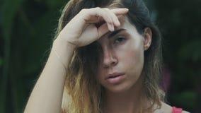 Een close-up van een bebouwd kader van een jong aantrekkelijk meisjes` s gezicht met kort donker haar en bruine naaktslakken, hou stock video