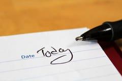 Een close-up van de blocnote met een penuiteinde en de woorden voor de datum vandaag wordt geschreven die royalty-vrije stock afbeelding