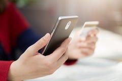 Een close-up van de vrouwelijke handen van ` s smartphone en creditcard die online betalend rekening via Internet houden, die tra royalty-vrije stock afbeeldingen