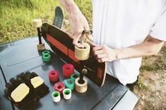 Een close-up van een jonge kerel verandert zijn wielen op zijn longboard en past de opschorting aan royalty-vrije stock foto