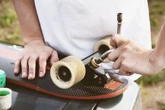 Een close-up van een jonge kerel verandert zijn wielen op zijn longboard en past de opschorting aan royalty-vrije stock foto's