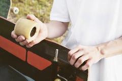 Een close-up van een jonge kerel verandert zijn wielen op zijn longboard en past de opschorting aan stock afbeelding