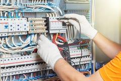 Een close-up van een elektroingenieur die in een machts elektropaneel werken stock foto's
