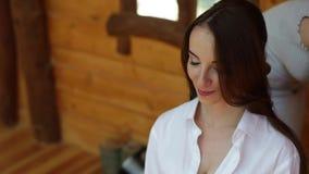 Een close-up van een herenkapper die haar van een mooie jonge bruid doen De bruid` s prijzen Een brunette stock videobeelden