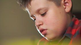 Een close-up van het gezicht van de jongen gebruikt een 3D pen Hij creeert een 3D cijfer van plastiek stock footage