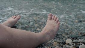 Een close-up van kind` s benen wordt overweldigd door een golf Kiezelsteen overzeese strand lawaaierige overzeese golven op kinde stock videobeelden