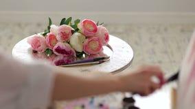 Een close-up van kunstenaar het schilderen bloemen die een borstel en een palet met behulp van stock footage