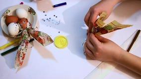 Een close-up van meisjes` s handen verfraait een wit ei met een gekleurd servet en een glanzend lint Grappige gezichten Decoratie stock footage