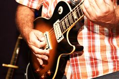 Een close-up van een mens die een elektrische gitaar spelen stock foto