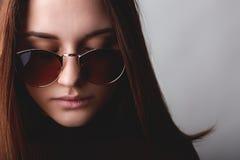 Een close-up van mooi meisje met bruin haar en zuivere huid die zonnebril dragen die nadenkende uitdrukking hebben terwijl neer h Stock Afbeeldingen