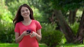 Een close-up van een mooie jonge vrouw in de aard die een telefoon en het typen houden Zij heft haar hoofd op en glimlacht stock video
