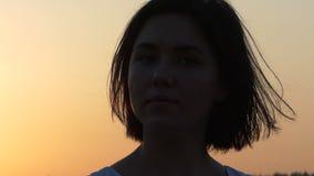 Een Close-up van Mooie Vrouwenwho bekijkt opzij en Draaien Zonsondergang in slo-Mo stock video