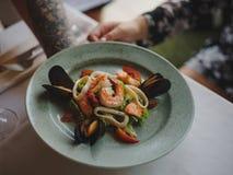 Een close-up van een plaat met zeevruchten, de dinerdienst en een glas wijn in kelners` s hand op een wit tafelkleed Stock Afbeeldingen