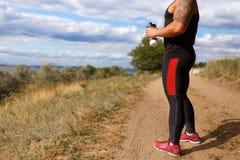 Een close-up van een spiermens op een landelijke wegachtergrond Een bodybuilder na een in openlucht opleiding Sportenconcept stock afbeeldingen