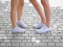 Een close-up van teenages` benen in witte tennisschoenen die aan elkaar op vaag spreken cobbled achtergrond De ruimte van het exe royalty-vrije stock afbeelding