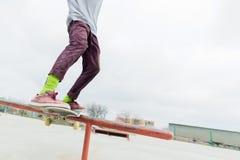 Een close-up van een tiener` s been van een skateboarder glijdt op een skateboard langs het traliewerk in skatepark Het concept royalty-vrije stock foto's
