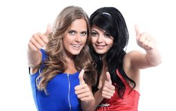 Een close-up van twee jonge meisjes die hun duimen tonen tegen Royalty-vrije Stock Foto's