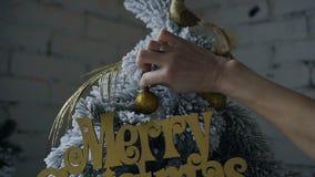 Een close-up van een vrouwen` s hand die een decoratieve Kerstboom met gouden ornamenten verfraait stock videobeelden