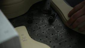 Een close-uparbeider maakt laser het merken van zolen van schoenen stock videobeelden
