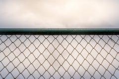 Een close-upbeeld van de roestige oude omheining van de kettingsverbinding met een duidelijke hemel in de loop van de dag tijd al Royalty-vrije Stock Afbeelding