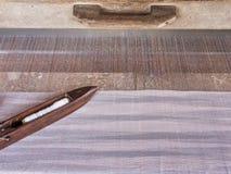 Een close-upbeeld van een oude houten pendel op eigengemaakte draden en wevend weefgetouw, traditionele textielproductie Stock Afbeeldingen