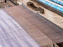 Een close-upbeeld van eigengemaakte draden en wevend weefgetouw, traditionele textielproductie Stock Fotografie