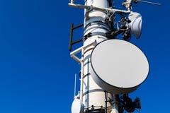 Een close-upbeeld van een telecommunicatieschotel op een toren op een blauwe achtergrond royalty-vrije stock afbeeldingen