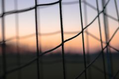 Een close-upbeeld van een voetbal netto met een zonsondergangzonsopgang op de achtergrond detail, sport, toekomst, dromen, spelvo stock foto's