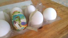 Een close-upfoto van één enkel geschilderd plastic paasei nestelde binnen van een plastic eikarton met verscheidene echte kippene stock afbeelding