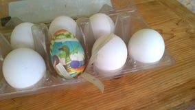 Een close-upfoto van één enkel geschilderd plastic paasei nestelde binnen van een plastic eikarton met verscheidene echte kippene stock foto