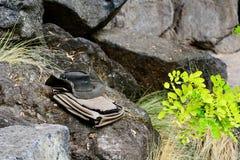 Een close-upfoto van een oude doorstane cowboyhoed en een reis doen in zakken, weggegaan op steen in de wildernis stock afbeelding