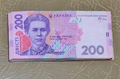 Een close-upfoto van een reeks van Oekraïens geld met een nominale waarde die van hryvnia 200, op een bruine leeroppervlakte ligg Stock Afbeeldingen