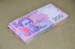 Een close-upfoto van een reeks van Oekraïens geld met een nominale waarde die van hryvnia 200, op een bruine leeroppervlakte ligg Stock Afbeelding