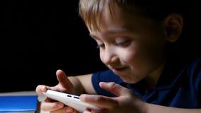 Een close-upkind bekijkt thuis een beeldverhaal bij nacht, gebruikend een smartphone, zit bij een lijst door een lamp wordt aange stock videobeelden