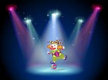 Een clown die boven de bal met schijnwerpers dansen Stock Foto's