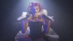 Een clownmeisje met het verbazen make-up zit onder de schijnwerper en past haar kleding aan stock videobeelden
