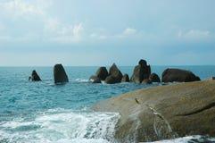 Een cluster van rotsen in het overzees, met het breken van golven Stock Fotografie