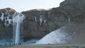 Een cluster van toeristen dichtbij de waterval stock video